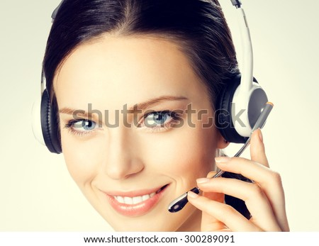 Portrait of smiling beautiful young female support phone operator in headset - stock photo
