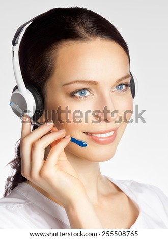 Portrait of smiling beautiful young support phone operator in headset, over grey - stock photo