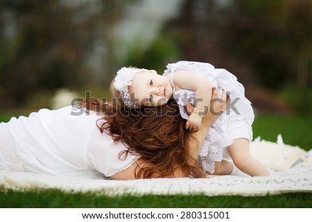 Portrait of smiling beautiful young woman and her little daughter sitting on grass, against green of summer park. - stock photo
