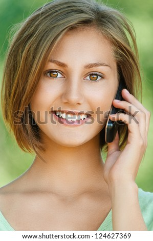 Portrait of smiling beautiful young woman close up with mobile phone, against background of summer green park. - stock photo