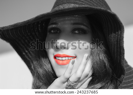Portrait of smiling beautiful young woman in  black raffia hat. Trendy fashion turquoise smoky eyes makeup. Sensual red  lips. Black white photo.  Model shooting on the beach. Hippie. Boho-chic. - stock photo