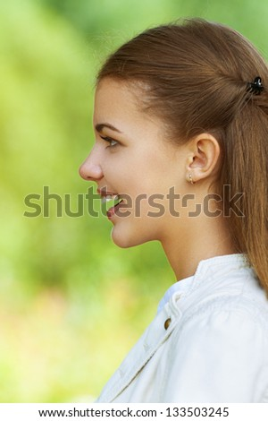 Portrait of smiling beautiful young woman profile, against background of autumn park.