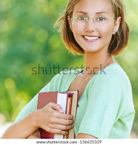 Portrait of smiling beautiful young woman-student with glasses, against background of summer green park. - stock photo
