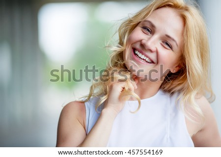 Portrait of smiling beautiful young woman touching her hair