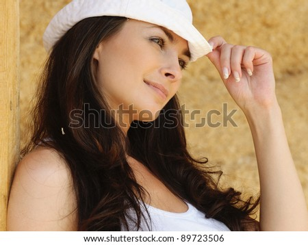 Portrait of smiling beautiful young woman wearing white cap and t-shirt against yellow background. - stock photo