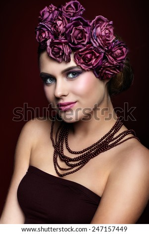 Portrait of smiling beautiful young woman with artificial rouses on head necklace and dress on red marsala color background