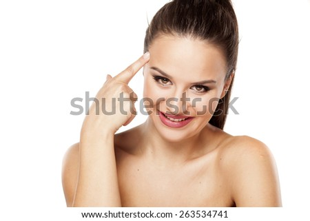 portrait of smiling beautiful young woman with the finger on forehead - stock photo