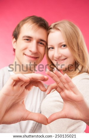 Portrait of smiling beauty girl and her handsome boyfriend making shape of heart by their hands. Happy joyful family. Love concept. Heart sign. Laughing happy lovers.  - stock photo
