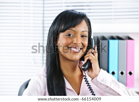 Portrait of smiling black business woman on phone in office - stock photo