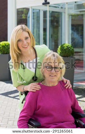 Portrait of Smiling Blond Nurse Standing Behind Senior Woman in Wheelchair Outdoors in front of Building on Sunny Day - stock photo