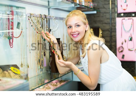 portrait of smiling blonde girl in dress choosing necklace in shop with bijouterie
