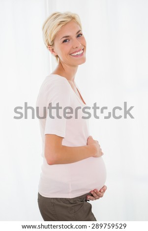 Portrait of smiling blonde pregnant with white background - stock photo