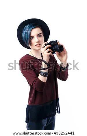 Portrait of smiling blue-haired girl in hat taking shot with film camera.Isolated
