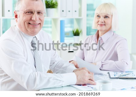 Portrait of smiling boss looking at camera at workplace with mature woman looking at him on background - stock photo