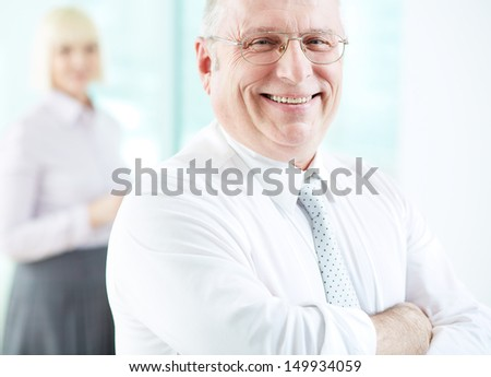 Portrait of smiling boss looking at camera with female on background - stock photo