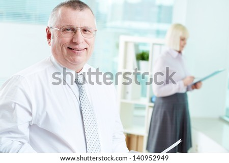 Portrait of smiling boss looking at camera with female standing on background - stock photo