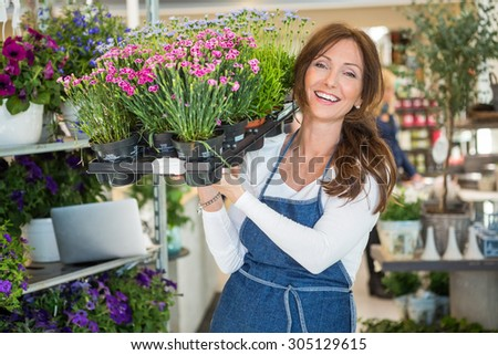 Portrait of smiling botanist carrying crate full of flower plants in store - stock photo