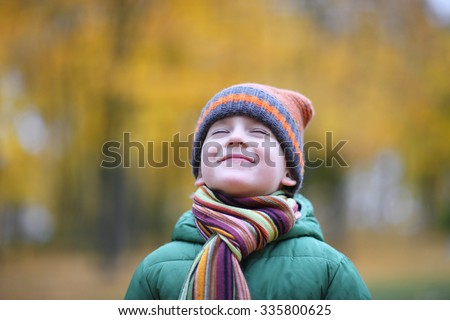 Portrait of smiling boy admiring autumn
