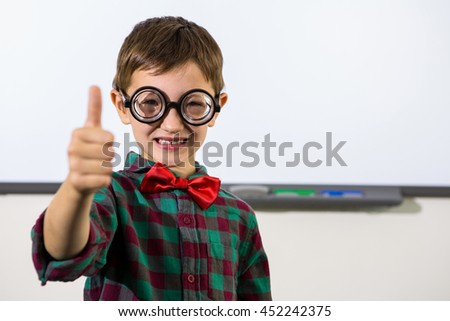 Portrait of smiling boy gesturing thumbs up sign in classroom - stock photo