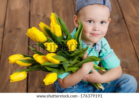 portrait of Smiling boy hiding a bouquet of yellow tulips sitting on wooden floor - stock photo