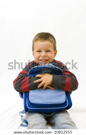 portrait of smiling boy holding a backpack in white background