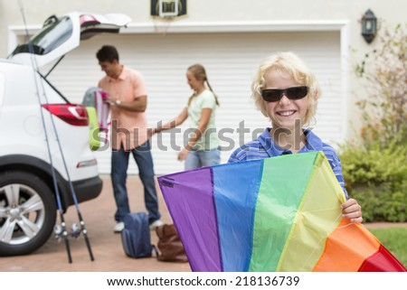 Portrait of smiling boy holding multicolor kite in driveway - stock photo