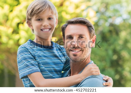 Portrait of smiling boy hugging his father. Father and son embracing and looking at camera outside. Cheerful father and son at park enjoying.