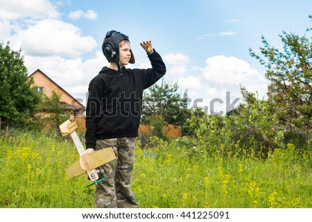 Portrait of smiling boy in pilot helmet with plane model on sky background looking ahead.  - stock photo
