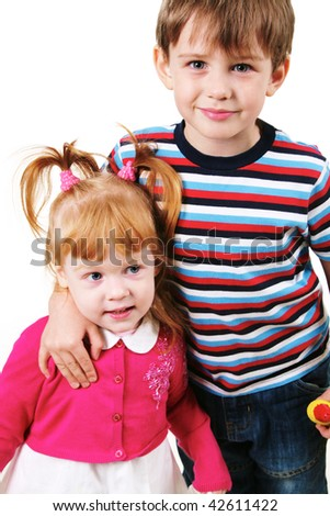 Portrait of smiling boy looking at camera while embracing his sister - stock photo