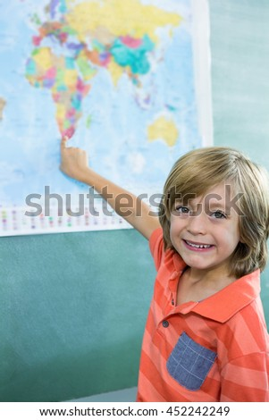 Portrait of smiling boy pointing on map in classroom - stock photo