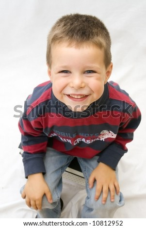 portrait of smiling boy sitting on big books with white background