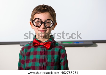Portrait of smiling boy standing against whiteboard in classroom - stock photo