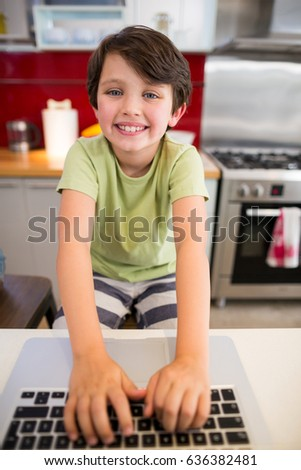 Portrait of smiling boy using laptop in kitchen at home