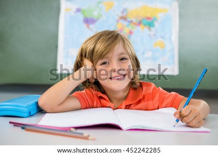 Portrait of smiling boy writing on book in classroom at school