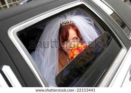 Portrait of smiling bride holding bouquer in wedding car limousine.