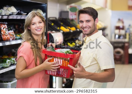 Portrait of smiling bright couple buying food products at supermarket