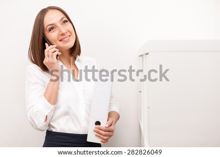 Portrait of smiling brunette businesswoman phoning while standing with a folder in office - stock photo