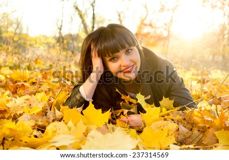 Portrait of smiling brunette woman lying on yellow leaves at autumn park - stock photo