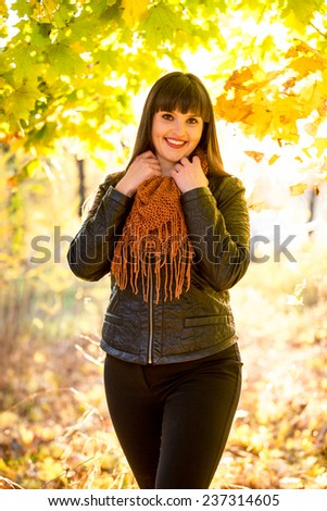 Portrait of smiling brunette woman posing at autumn park at sunny day - stock photo