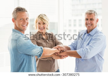 Portrait of smiling business colleagues stacking hands at the office