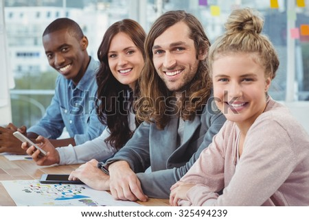 Portrait of smiling business people at desk in office - stock photo