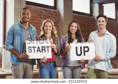 Portrait of smiling business people showing card with start up text while standing in creative office
