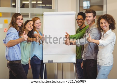 Portrait of smiling business people showing thumbs up white standing by whiteboard during meeting in office - stock photo