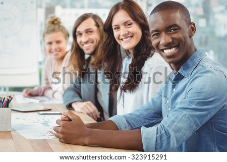 Portrait of smiling business people sitting in row at desk in office