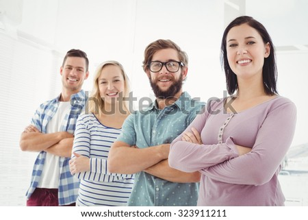Portrait of smiling business people standing in row with arms crossed at office - stock photo