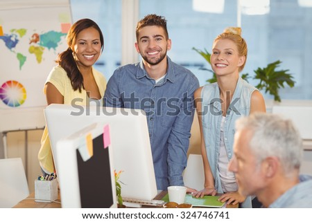Portrait of smiling business people using computer as male colleague working in creative office - stock photo