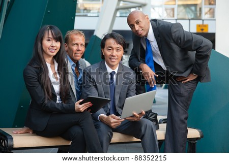 Portrait of smiling business people using electronic gadgets - stock photo