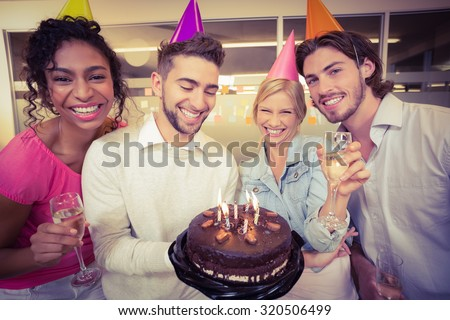 Portrait of smiling business people with birthday cake enjoying the party in creative office - stock photo