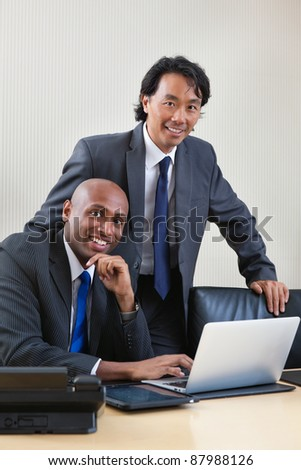 Portrait of smiling business people working on laptop - stock photo