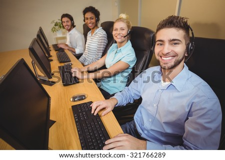 Portrait of smiling business people working together in call center